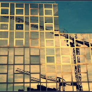 reflets de grue sur facade de verre